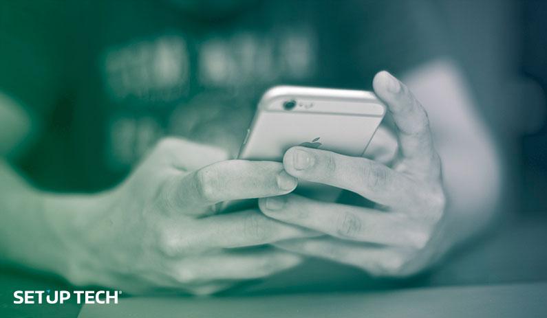 Homem a utilizar smartphone: Competitividade: vantagens do software personalizado