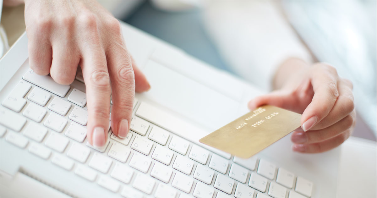 Mulher a usar um cartão de crédito e um computador (e-commerce)